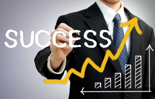 Businessman writing success with a rising arrow above a bar graph